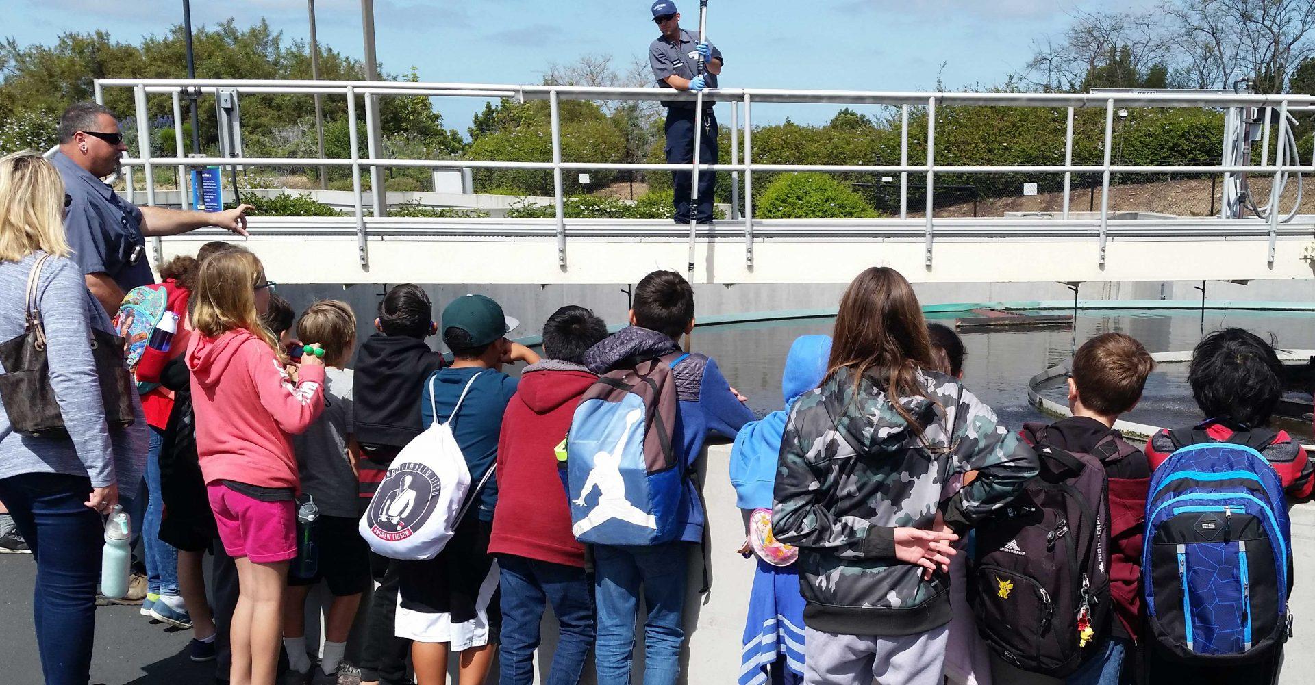 Children stand around clarifier at water treatment plant