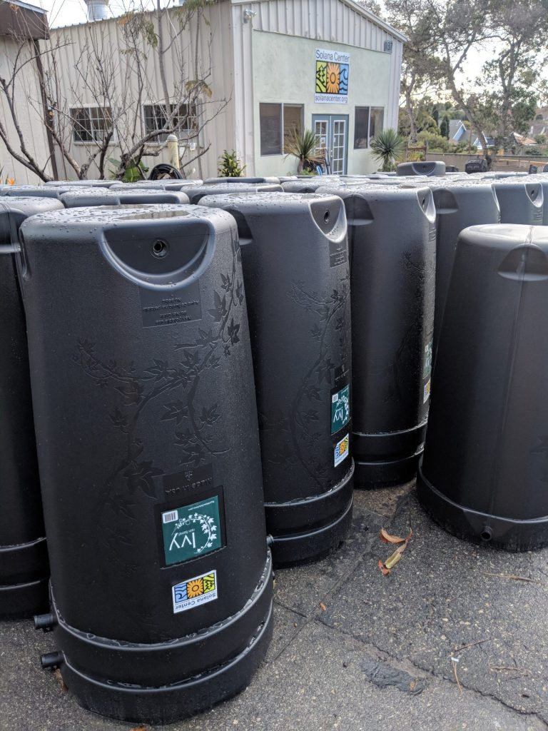 Rain barrels lined up near a building